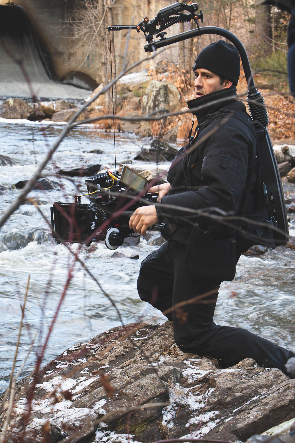 Near the river, the DOP is waiting for the next scene. Arm with his camera and stabilization equipment we make sure not to slip into the water.